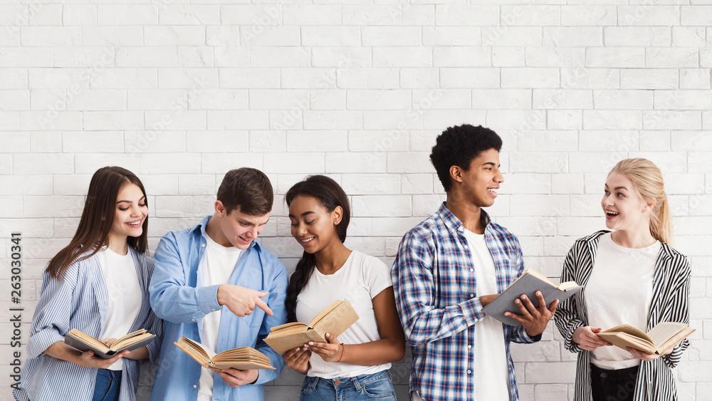 Fototapeta Exam preparation. Teenagers with books standing over light wall