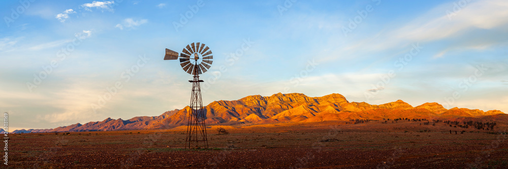Fototapeta A windmill with the Flinders Ranges behind it in the Australian outback. Flinders Ranges National Park, South Australia, Australia.