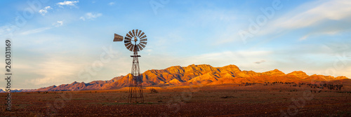 Fotobehang Diepbruine A windmill with the Flinders Ranges behind it in the Australian outback. Flinders Ranges National Park, South Australia, Australia.