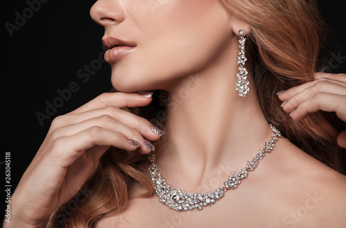 Leinwand Poster Beautiful young woman with elegant jewelry on dark background, closeup