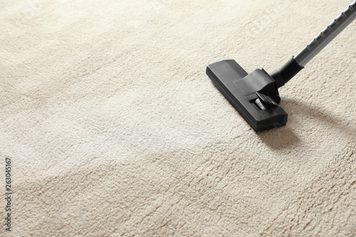 Foto Removing dirt from light carpet with vacuum cleaner