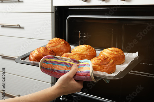 Valokuva  Woman taking freshly baked buns out of oven, closeup