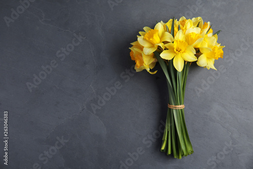 Photo Bouquet of daffodils on dark background, top view with space for text