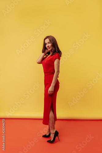 Fotografía  Full-lenght photo pretty woman wearing elegant red dress and heels on red and yellow background