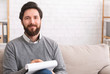 Bearded male psychotherapist writing on clipboard and smiling
