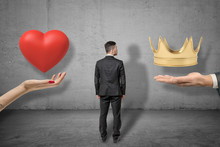 Young Businessman Standing Between Two Big Hands Holding Red Heart And Golden Crown On Grey Wall Background. Background