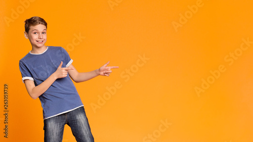 Fotografía  Cheerful teen boy pointing two fingers aside at free space
