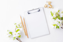 Flat Lay Blogger Or Freelancer Workspace With A Mockup Clipboard And Spring White Flower On A White Table