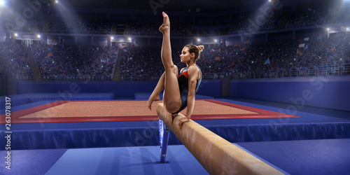 Fotografia Female athlete doing a complicated exciting trick on gymnastics balance beam in a professional gym