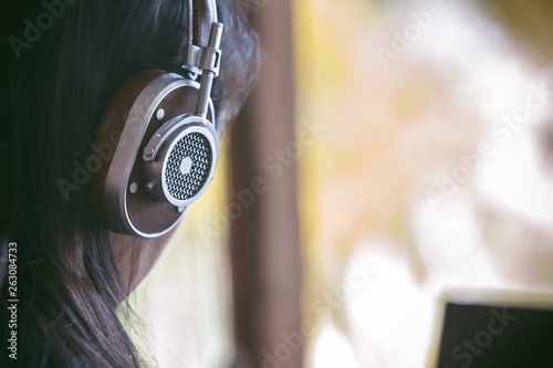 Headphones with long hair women,The back of the woman with headphones,Woman listening music in coffee shop, - 263084733