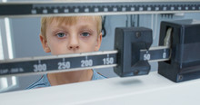 Close Up Of Little Boy Being Weighed On Scale At Pediatrician. Child Patient Visiting Doctor For Regular Check Up