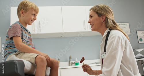 Little boy at pediatric office checking his reflexes with hammer while doctor watches. Female pediatrician showing patient how reflex hammer works