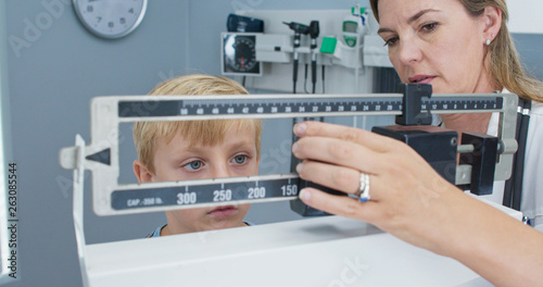Stampa su Tela  Doctor weighing little boy patient on scale in exam room