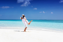 Happy, Young Couple In White Summer Clothes Enjoying Their Vacation On A Tropical Beach