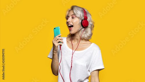 Portrait of happy cute girl listening to music and singing in mobile phone. Pretty lady wearing modern red headphones. Technology and fun concept. Copy space in right side. Isolated on yellow - 263094793