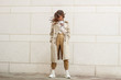Leinwanddruck Bild - Portrait shooting of a stylish girl. Beige shades. Trends of spring and summer 2019. Pants of cork.Trench cloak, a wide jacket.