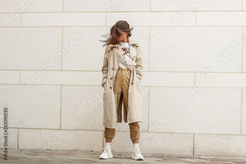 obraz PCV Portrait shooting of a stylish girl. Beige shades. Trends of spring and summer 2019. Pants of cork.Trench cloak, a wide jacket.