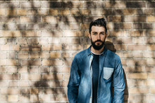 Handsome Serious Man In Denim Shirt With Beard Over Brick Wall In Sunlight.