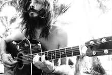 Portrait Of A Handsome Hippie Guy With A Guitar