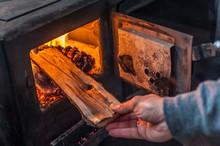 Man Putting Log To Wood Burnin...