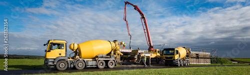 Photo Baufahrzeuge auf einer Baustelle - Gelber Betonmischer im Vordergrund