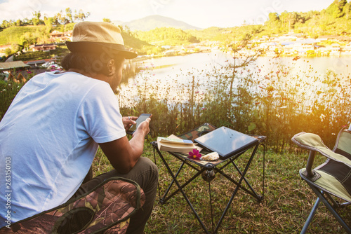 Tuinposter Zwavel geel Asian men are using the phone to search for tourist information, Travel nature, Travel relax, Concept of Camping Relaxing Tourism in village Countryside.