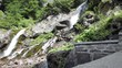 Mountain stream in rocky cliff side in forest clearing
