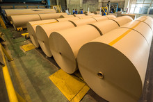 Mechanical Equipment And Yellow Board Paper Products Produced In A Paper Mill Workshop