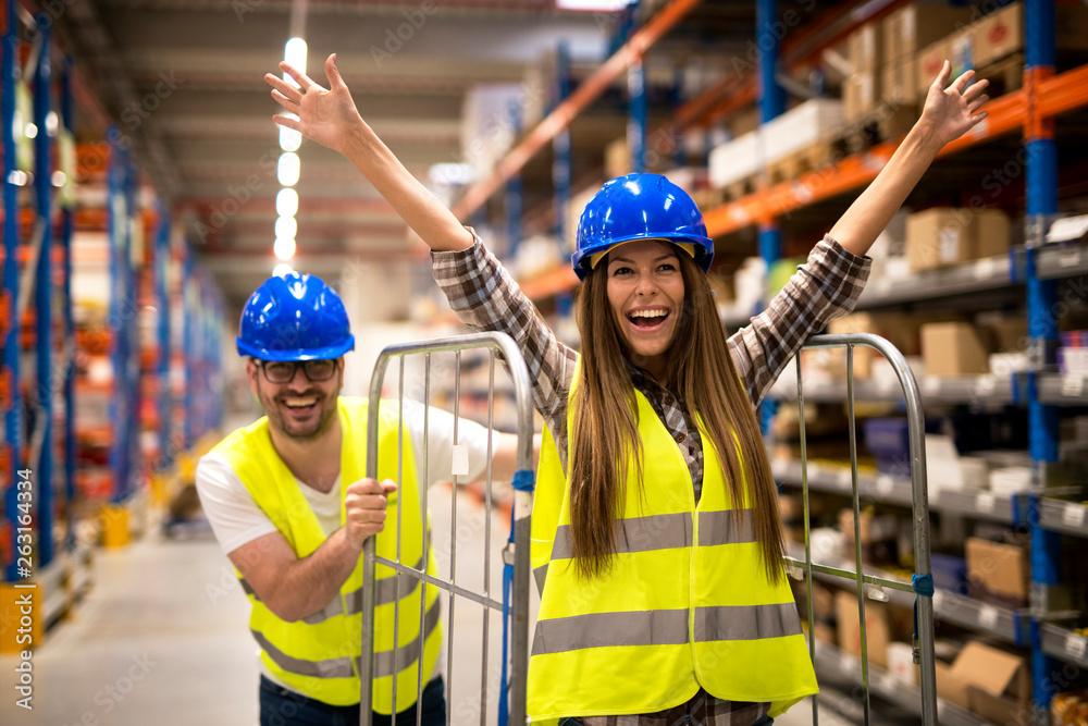 Fototapeta Positive people having fun at work. Warehouse workers pushing carts and enjoying in storage room.