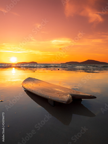 Fototapeten See sonnenuntergang surfboard on the beach in sea shore at sunset time