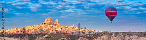 Foto auf Gartenposter Ballon Panoramic view of the Turkish fortress Uchisar in the morning and one hot air balloon, landscape of Goreme in Cappadocia, Turkey.