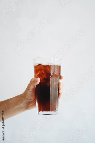 Hand holding a glass of homemade cold brew coffee on white table Canvas Print