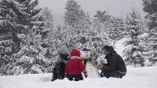 Family Building A Snowman In P...