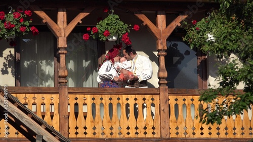 Fotografie, Obraz  Man, woman and baby with traditional clothes at wooden house balcony, parents ki