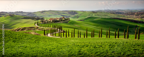 Tuscan hill with row of cypress trees and farmhouse at sunset Fotobehang