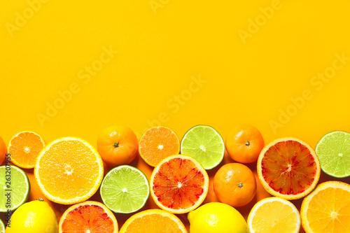 Carta da parati  Different citrus fruits on color background, flat lay