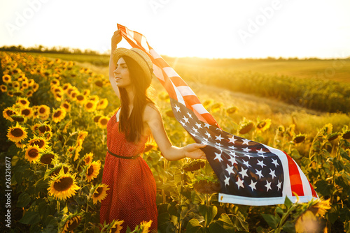 Fotografía  Beautiful girl in hat with the American flag in a sunflower field