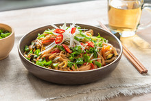 Asian Vegan Lunch - Spicy Chow Mein Noodles With Carrots, Pepper And Spinach With Sliced Radish, Spring Onions And Chili Peppers On A Rustic Table