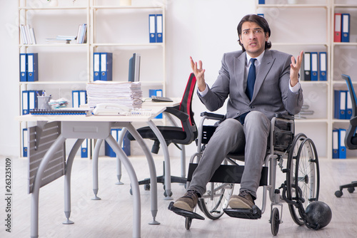 Fototapety, obrazy: Young handsome employee in wheelchair working in the office