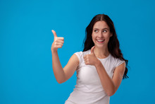 Smiling Woman Giving Thumbs Up On Blue Background