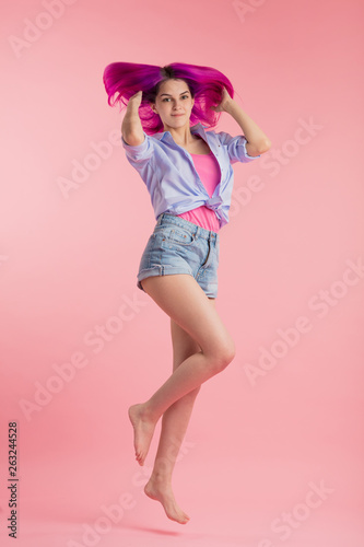 lovely positive crazy girl in good mood jumping over pink background, lifestyle, optimism, amorous girl is ready to fly