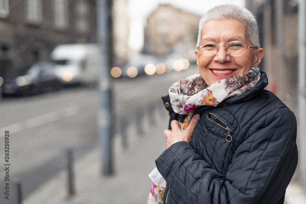 Fototapety, obrazy: Portrait of beautiful senior woman with a jacket on a windy day in an urban city environment, happy and cheerful