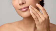 Woman Applying Lip Balm Over Grey Background