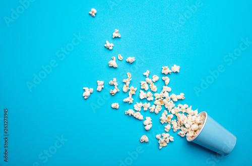 Fotografering  Pop corn scattered on blue color background, top view