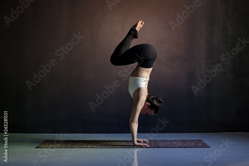 woman practicing yoga, Adho Mukha Vrksasana exercise, Downward facing Tree pose Canvas Print