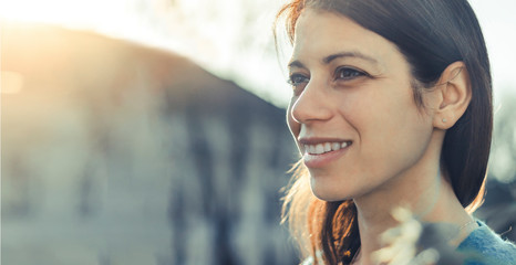 Closeup of a smiling young woman looking into the distance at sunset.