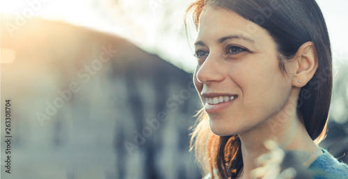 Obraz Closeup of a smiling young woman looking into the distance at sunset. - fototapety do salonu