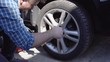 Man screwing car wheel with summer tire on a driveway. Seasonal tyre change or service abstract concept.