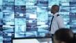 4K Security team watching CCTV screens in control room officer talking on radio