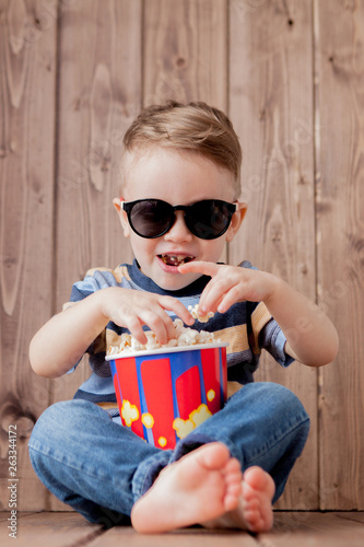 фотография Little cute kid baby boy 2-3 years old , 3d imax cinema glasses holding bucket for popcorn, eating fast food on wooden background
